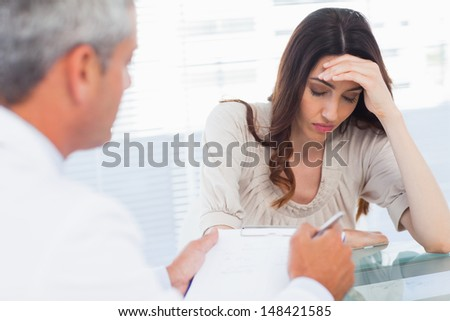 Upset woman listening to her doctor talking about a illness in medical office - stock photo