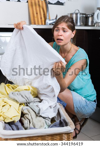 Upset  woman looking at clothes with persistent stains after laundry - stock photo