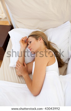 Upset woman lying on her bed