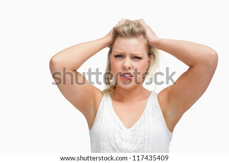 Upset woman standing while placing her hands on her head against a white background