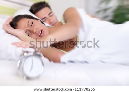 Upset woman turn off alarm clock, Wake up early morning.