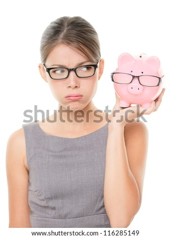 Upset woman wearing glasses holding piggy bank. Expensive eyewear glasses concept. Young female business woman isolated on white background. - stock photo