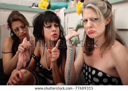 Upset woman with drunk friends on phone in kitchen - stock photo