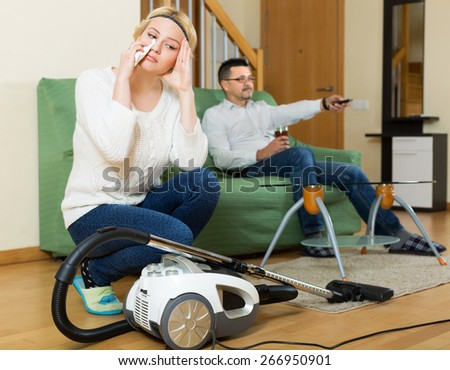 Upset woman with hoover looking at tired man on sofa watching TV