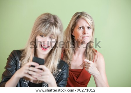 Upset woman with laughing teen on cell phone - stock photo