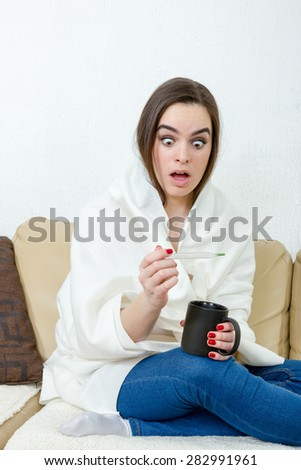 Upset woman with thermometer sick colds, flu, fever and migraine in bed with cup of tea or coffee. Girl with high temperature and headache virus. Female caught cold covered with white blanket at home. - stock photo