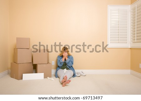 Upset Woman with Tissues on Floor Next to Boxes and Blank Sign in Empty Room. - stock photo