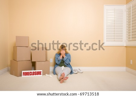 Upset Woman with Tissues on Floor Next to Boxes and Foreclosure Real Estate Sign in Empty Room. - stock photo
