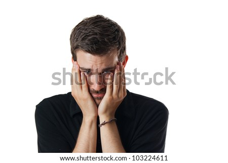 Upset worried young man with his face clasped in his hands and head bowed isolated on white - stock photo