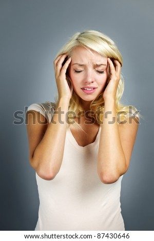 Upset young blonde woman with headache on grey background - stock photo
