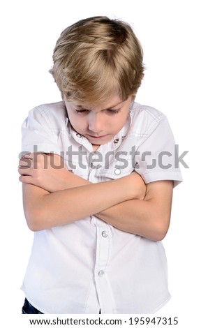 upset young boy with crossed arms on white