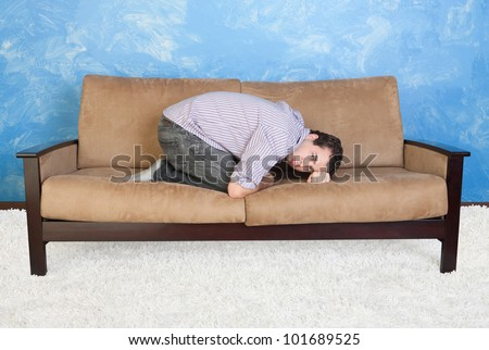 Upset young Caucasian man in fetal position on sofa - stock photo