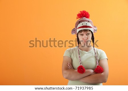 Upset young Caucasian woman on an orange background - stock photo