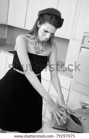 Upset young Caucasian woman slams down phone receiver - stock photo
