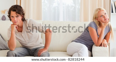 Upset young couple sitting on a couch with their hand on their chin - stock photo
