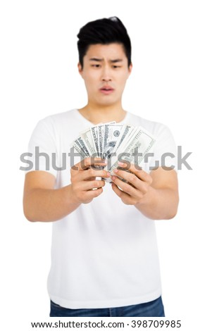 Upset young man counting fanned out currency notes on white background