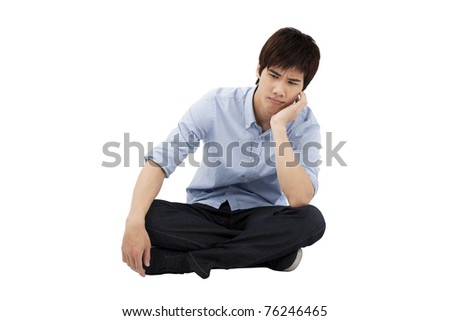 upset young man sitting on the floor - stock photo
