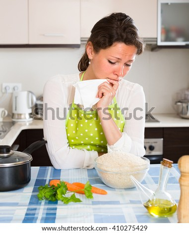 Upset young woman cooking dinner for her family at home kitchen - stock photo