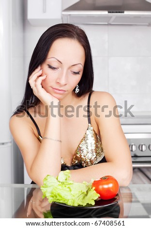 upset young woman keeping a diet and eating vegetables in the kitchen at home - stock photo