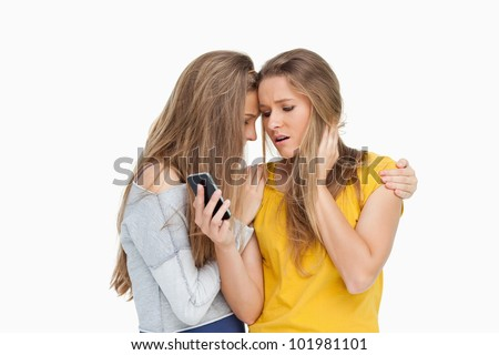 Upset young woman looking her cellphone consoled by her friend against white background