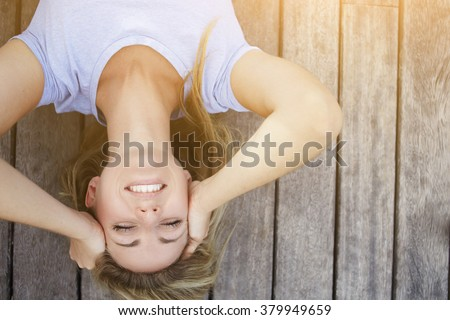 Upside down image of a young blonde woman with beautiful smile lying on a wooden floor in the fresh air, happy cheerful hipster girl posing for camera with copy space for your advertising text message - stock photo