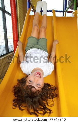 upside down little girl on playground slide laughing happy - stock photo