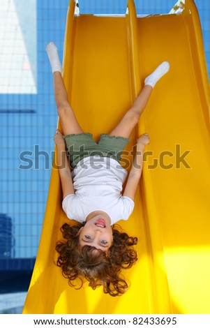 upside down little girl on playground slide laughing in modern city buildings [Photo Illustration] - stock photo