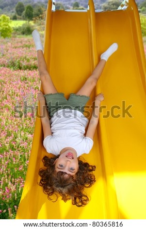 upside down little girl on playground slide laughing in pink flower meadow [Photo Illustration] - stock photo