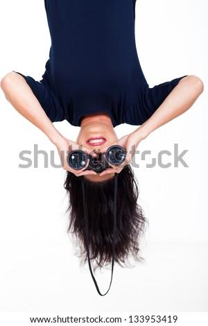upside down photo of young woman holding binoculars - stock photo