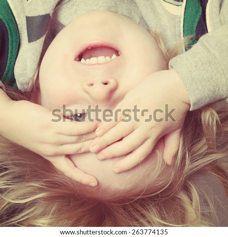 Upside down toddler boy playing peek a boo. Instagram effect. - stock photo