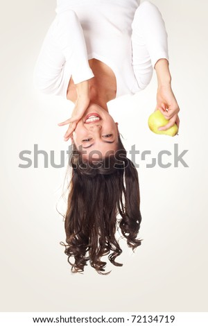 Upside down view of happy girl with pear in hand on white background - stock photo