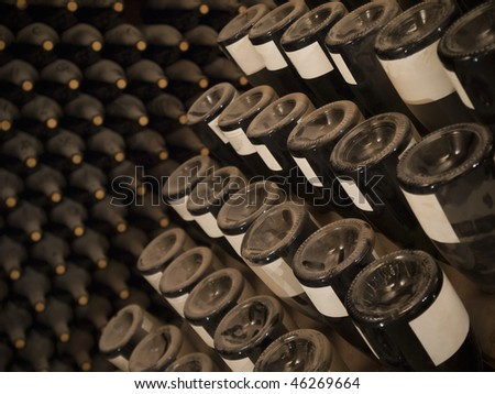 Upside down wine bottles in a rack. More bottles on the background.