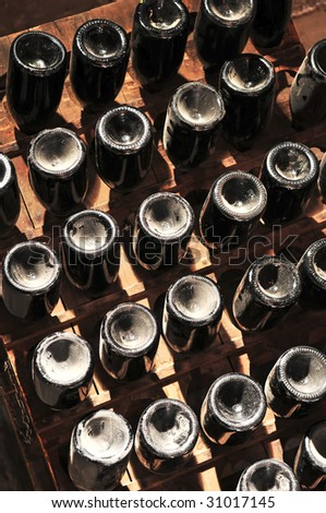 Upside down wine bottles maturing in wooden racks - stock photo