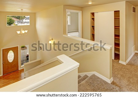 Upstairs hallway with staircase with view on entrance hallway - stock photo