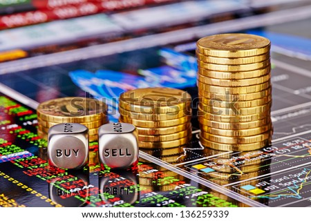 Uptrend stacks golden coins, dices cubes with the words SELL BUY on the financial stock charts as background. Selective focus - stock photo
