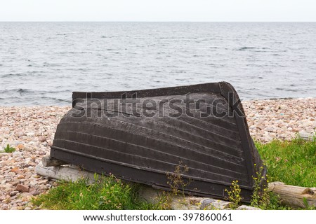 Upturned rowboat on the beach - stock photo