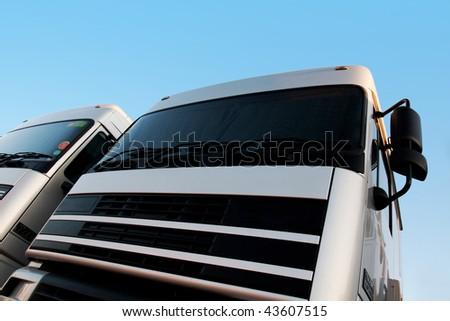 Upward angle view of two semi-trailer trucks. - stock photo