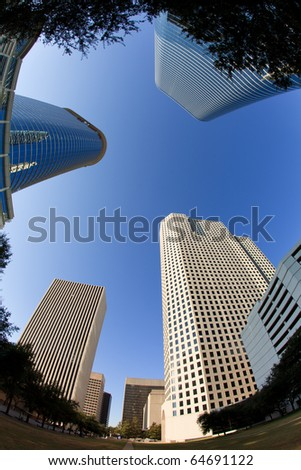 Upward fish eye view of tall skyscrapers against a blue sky in the downtown business area of Houston, Texas.