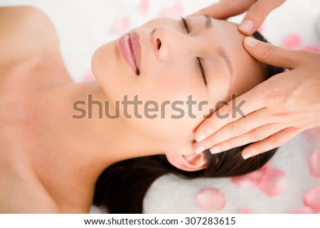 Upward view of an attractive young woman receiving facial massage at spa center