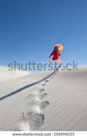 Upward view of attractive and happy looking mature woman walking up a white sand dune, leaving footsteps, with red blouse, matching umbrella, isolated with clear blue sky as background and copy space. - stock photo