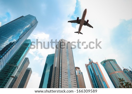 upward view of modern building with airplane in shanghai  - stock photo