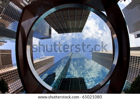 Upward view of tall skyscrapers against a blue sky and clouds in the downtown business area of Houston, Texas. - stock photo