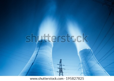 upward view of the cooling towers in a power plant at night  - stock photo