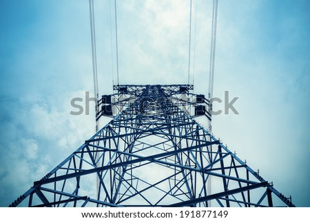 upward view of the power transmission tower in a cloudy sky  - stock photo