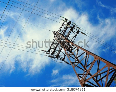 Upward view on power lines on a background of blue sky with clouds - stock photo