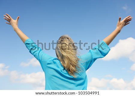Upwards view of young woman enjoying life - stock photo