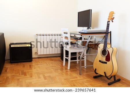 Urban apartment - computer and guitar - stock photo