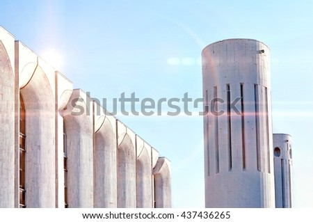 Urban architecture -concrete walls and columns built in futuristic style. Architecture cold toned modern background of architecture cityscape with stylized cosmic reflected lights over architecture.