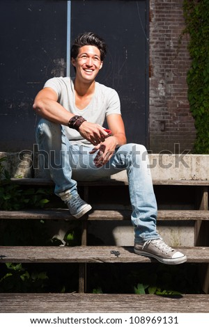 Urban asian man sitting on stairs. Good looking. Cool guy. Wearing grey shirt and jeans. Old neglected building in the background. - stock photo