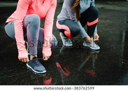Urban athletes lacing sport footwear for running over asphalt under the rain. Two women getting ready for outdoor training and fitness exercising on cold winter weather. - stock photo